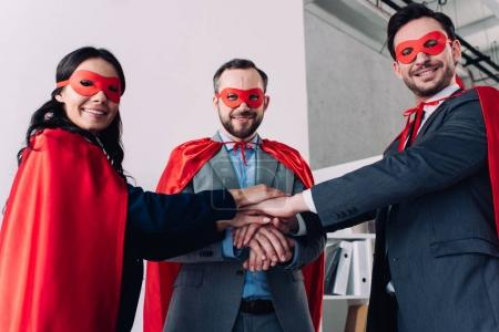 super businesspeople in masks and capes putting hands together in office