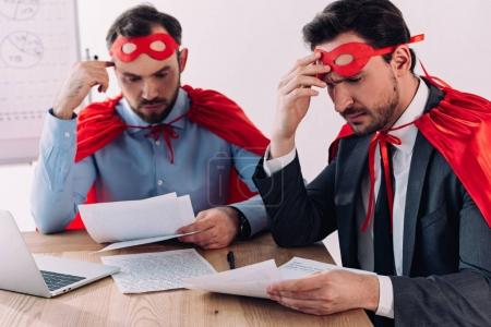 pensive handsome super businessmen in masks and capes working with papers in office