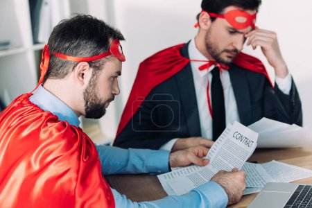 handsome super businessmen in masks and capes working with papers in office