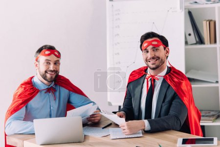 smiling handsome super businessmen in masks and capes looking at camera in office