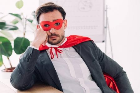 surprised super businessman in mask and cape looking at camera in office