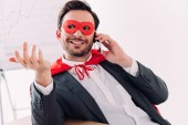 handsome super businessman in mask and cape talking by smartphone in office