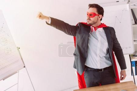 handsome super businessman in mask and cape standing with hand up in office