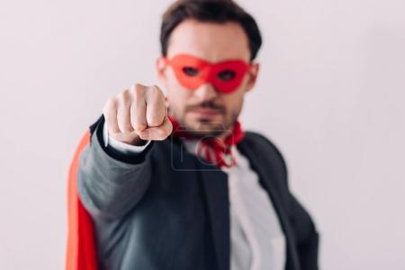 Photo for Handsome super businessman in mask and cape showing fist isolated on white - Royalty Free Image