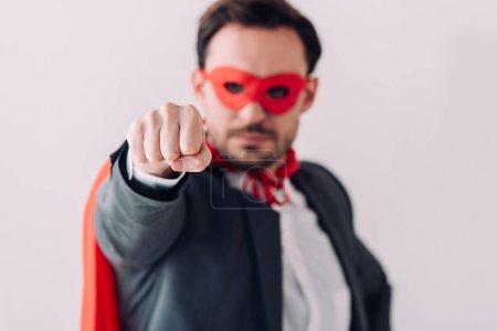 Photo pour Beau super homme d'affaires en masque et cape montrant poing isolé sur blanc - image libre de droit