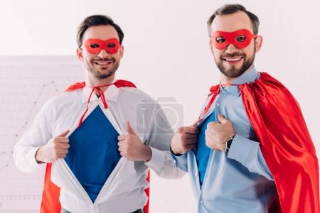 handsome super businessmen in masks and capes showing blue shirts in office