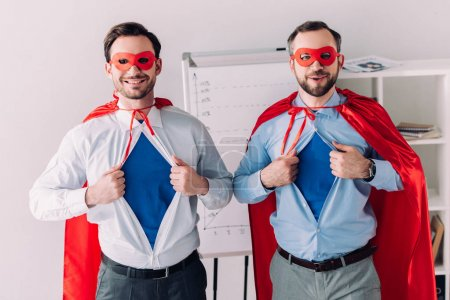 smiling handsome super businessmen in masks and capes showing blue shirts in office