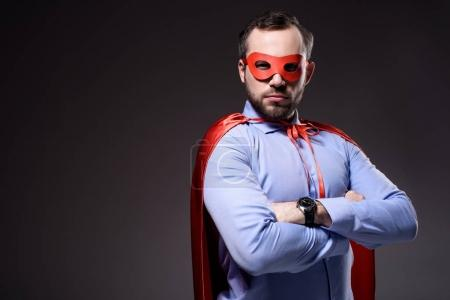 handsome super businessman in mask and cape with crossed arms isolated on black