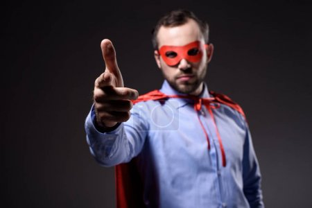 handsome super businessman in mask and cape pointing on camera isolated on black