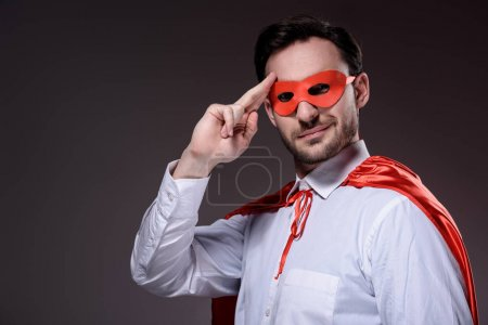 handsome super businessman in mask and cape saluting isolated on black