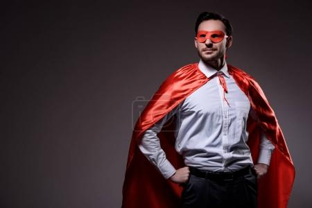 handsome super businessman in mask and cape standing with hands akimbo isolated on black