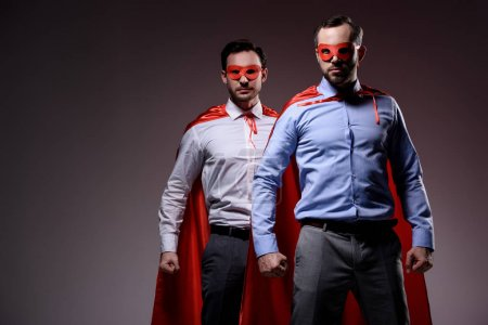 handsome super businessmen in masks and capes standing with fists isolated on grey
