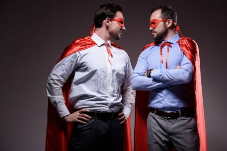 handsome super businessmen in masks and capes looking at each other isolated on grey