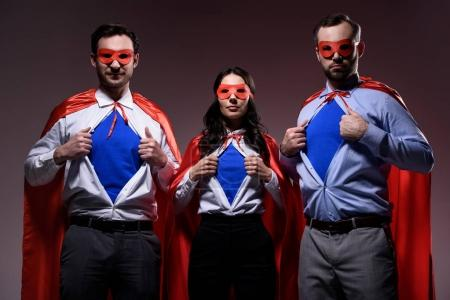 super businesspeople in masks and capes showing blue shirts isolated on grey