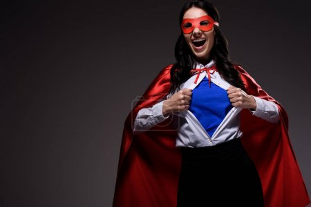 Photo for Laughing attractive super businesswoman in red cape and mask showing blue shirt isolated on black - Royalty Free Image