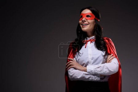 smiling attractive super businesswoman in red cape and mask standing with crossed arms isolated on black