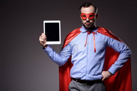 handsome super businessman in mask and cape holding tablet isolated on black