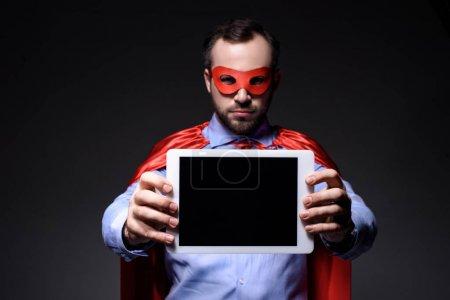 empresario super guapo en máscara y capa mostrando tableta aislada en negro