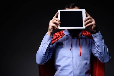 super businessman in cape covering face with tablet isolated on black