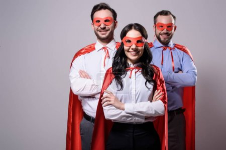 smiling super businesspeople in masks and capes with crossed arms isolated on grey