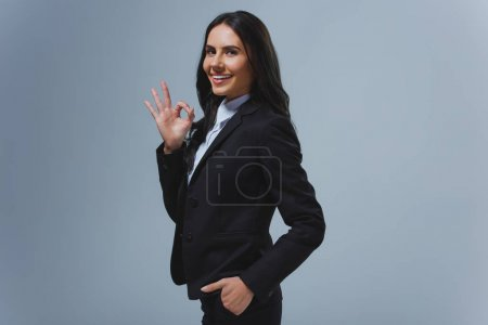smiling attractive businesswoman showing okay gesture isolated on grey
