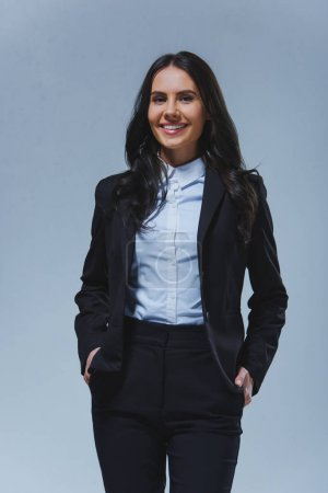 smiling attractive businesswoman looking at camera isolated on grey