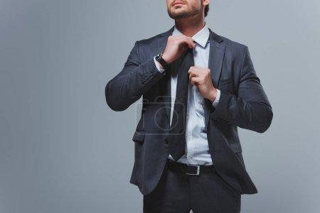 Foto de Imagen recortada de empresario fijación lazo aislado en gris - Imagen libre de derechos