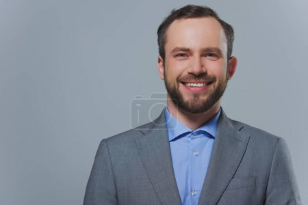 Photo for Smiling handsome businessman looking at camera isolated on grey - Royalty Free Image