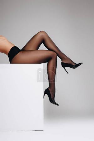 Photo pour Slim femme en collants noirs, assis sur une boîte blanche isolée sur fond gris - image libre de droit