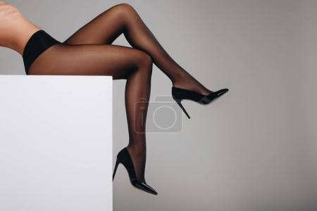 Photo for Woman in black pantyhose and heel shoes posing on white box isolated on grey - Royalty Free Image