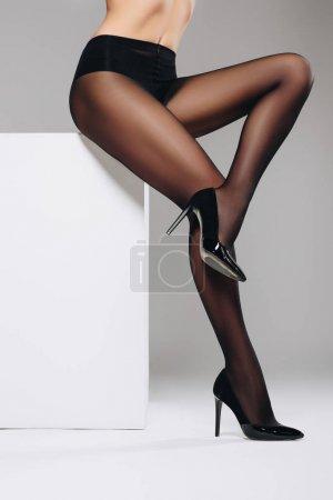 Photo pour Femme sensuelle en nylon noir collants posant sur boîte blanche - image libre de droit
