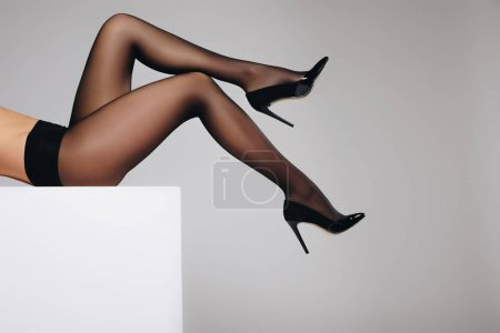 Female legs in black pantyhose isolated on grey background