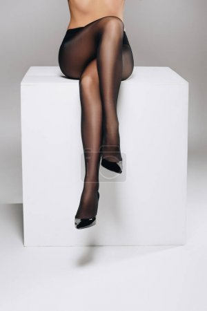 Photo for Woman wearing black pantyhose posing on white box with legs crossed - Royalty Free Image