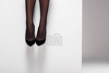 Photo pour Jambes féminines en collants noirs et chaussures sur fond blanc - image libre de droit