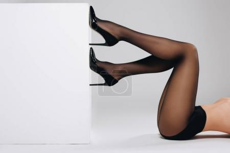 Female legs in black pantyhose on white background