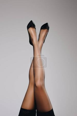 Photo for Woman wearing black stockings with legs crossed isolated on grey background - Royalty Free Image