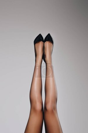 Female legs in black stockings isolated on grey background