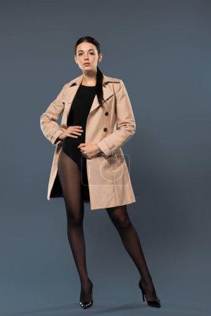 Photo pour Femme mince en collants noirs et tranchée beige sur fond sombre - image libre de droit