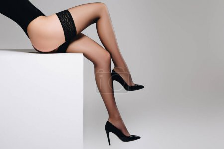 Sensual woman in black nylon stockings sitting on white box isolated on grey