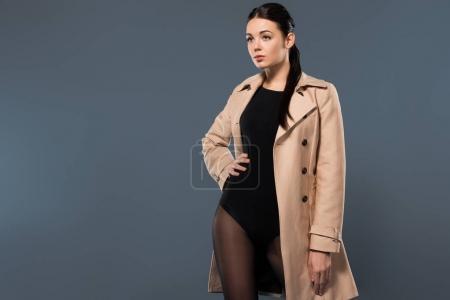 Photo pour Femme en collants noirs et tranchée beige isolé sur fond sombre - image libre de droit