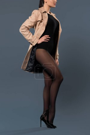 Sensual woman in black nylon pantyhose and beige trench on dark background
