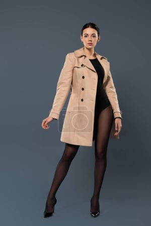 Woman in black pantyhose and heel shoes wearing trench on dark background