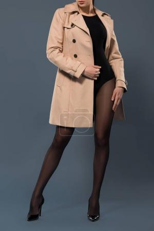 Sensual woman in black nylon tights wearing beige trench on dark background