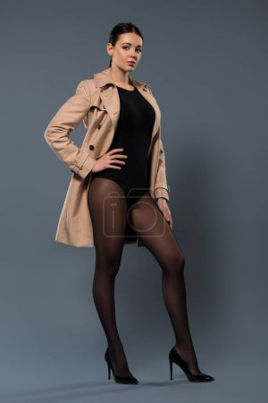 Woman posing in black pantyhose and beige trench on dark background