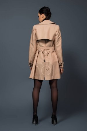 Rear view of woman in black pantyhose and beige trench on dark background