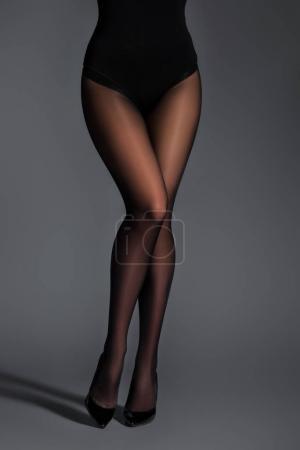 Photo pour Jambes féminines en collants noirs sur fond sombre - image libre de droit