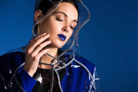 Dreamy woman with blue lipstick wearing raincoat isolated on blue background
