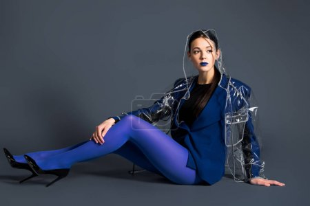 Slim woman in blue pantyhose and raincoat lying on dark background