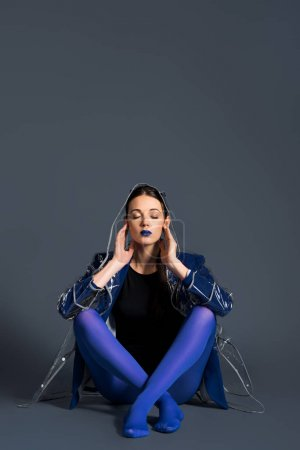 Girl wearing transparent raincoat and blue pantyhose sitting on dark background