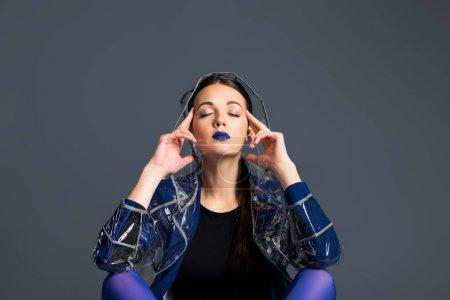 Photo pour Jeune femme en imperméable transparent rêve isolé sur fond foncé - image libre de droit